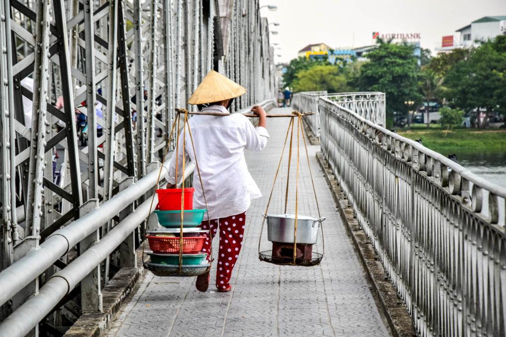 Une dame traverse un pount à Hué