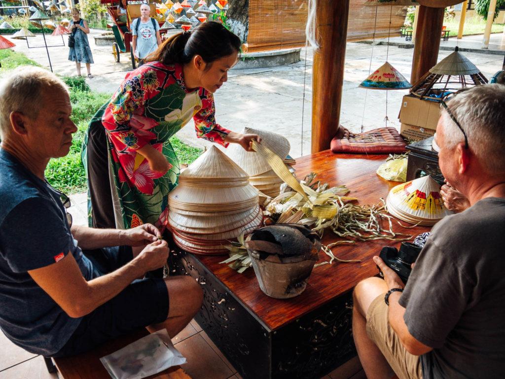 Une vietnamienne apprend à des touristes à faire un chapeau