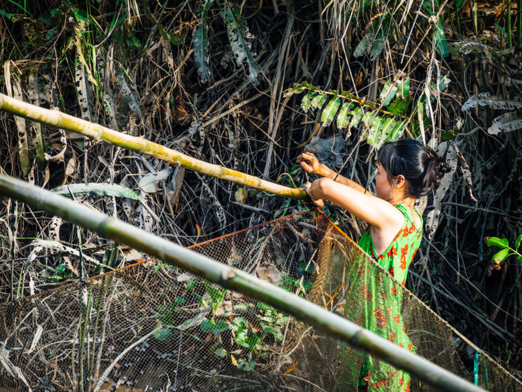 Une dame réglant son filant dans le mékong