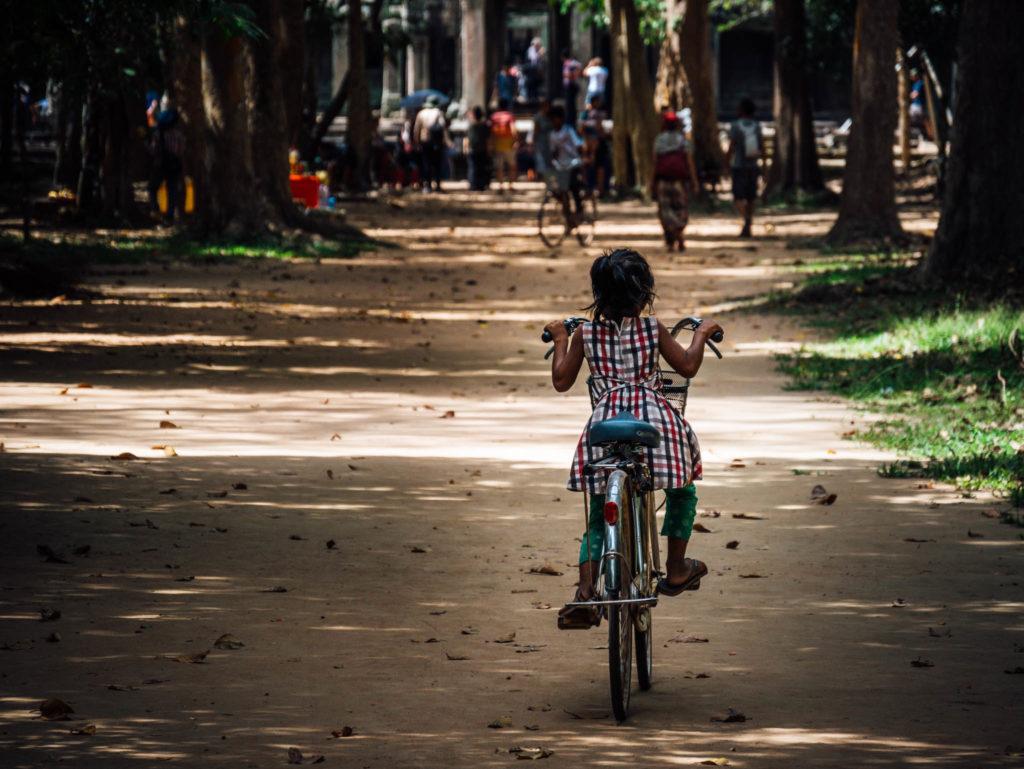 Une gamine faisant du vélo dans les temples