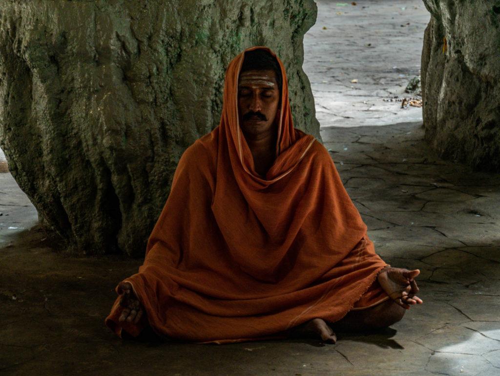 Un homme méditant ou priant dans la grotte